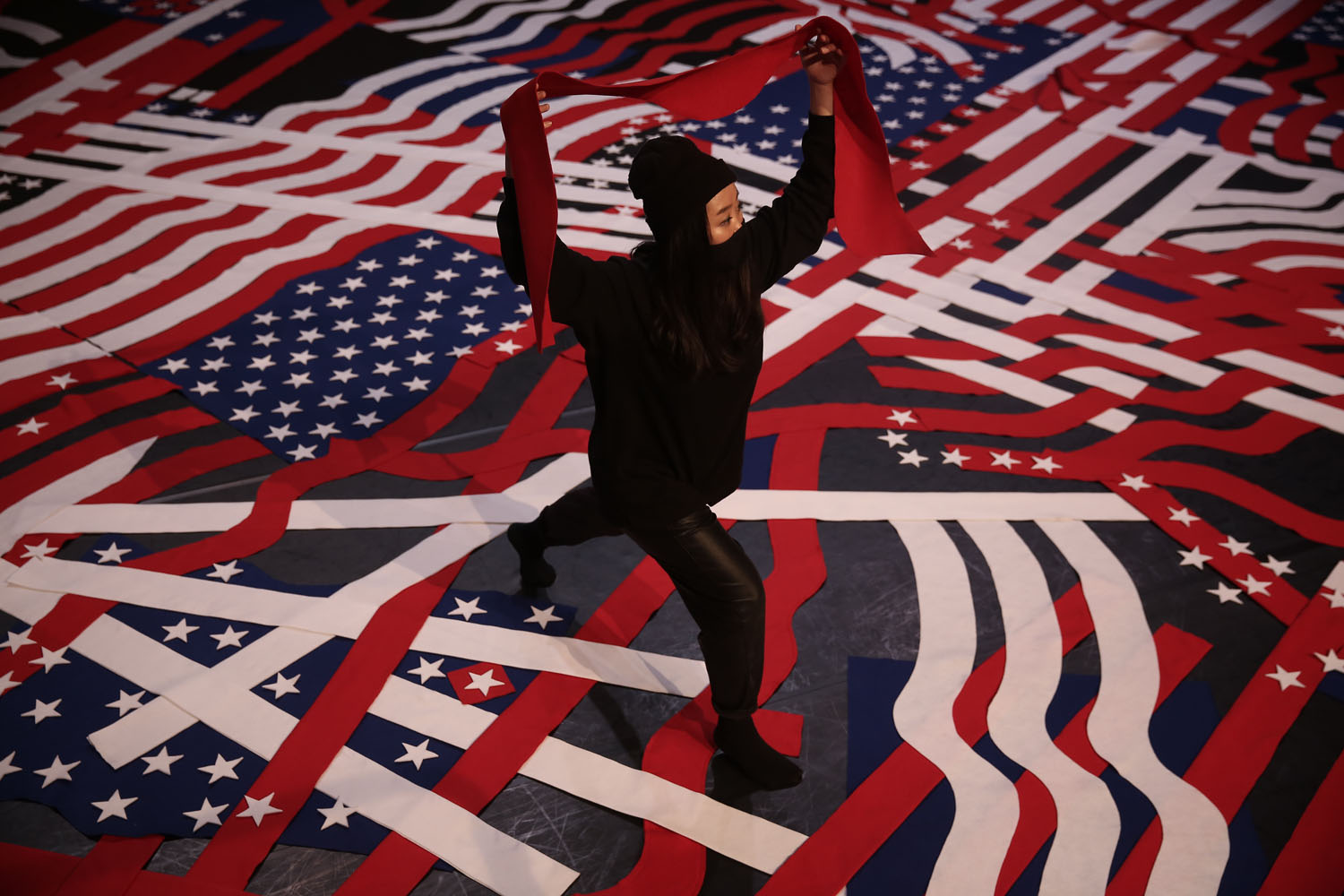 Artist making a large scale collage using the elements of American flag on the floor of Queenslab, the Kitchen's project space