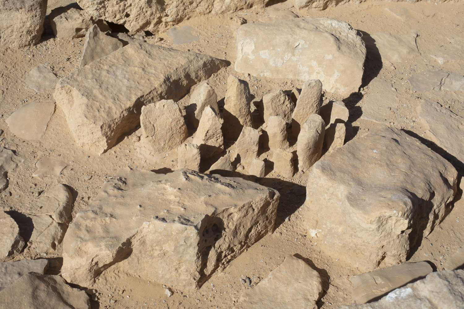 A cluster of roughly conical shaped stones are arranged on the desert floor surrounded by a square of four large rectangular shaped stones.