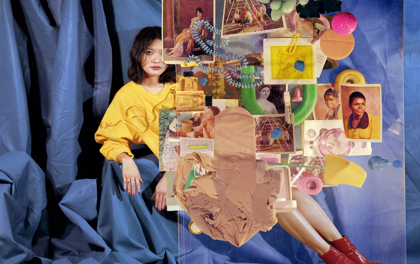 A woman sits behind a collage made of old photographs, pantyhose, perfume bottles, and other feminine items. Her legs, showing from behind the collage, are shiny and her feet are fitted with red boots. Her right arm, both hands, one with a ring on it, and half of her face including one eye, are visible.