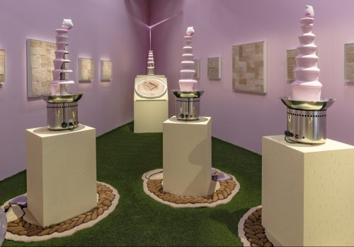 A light pink painted triangular room with green wall to wall astroturf flooring. From this perspective you can see three 6- tiered chocolate fondue fountains, but instead of chocolate they are filled with Lusters Pink Oil Moisturizer Lotion. Topping each of the fountains is a Sqweel 2 oral sex toy, the kind that is white with little pink silicone