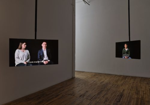In a white room with wooden floors, two tv screens are hanging. The left screen shows two Kosovars talking to the camera, with the caption reading