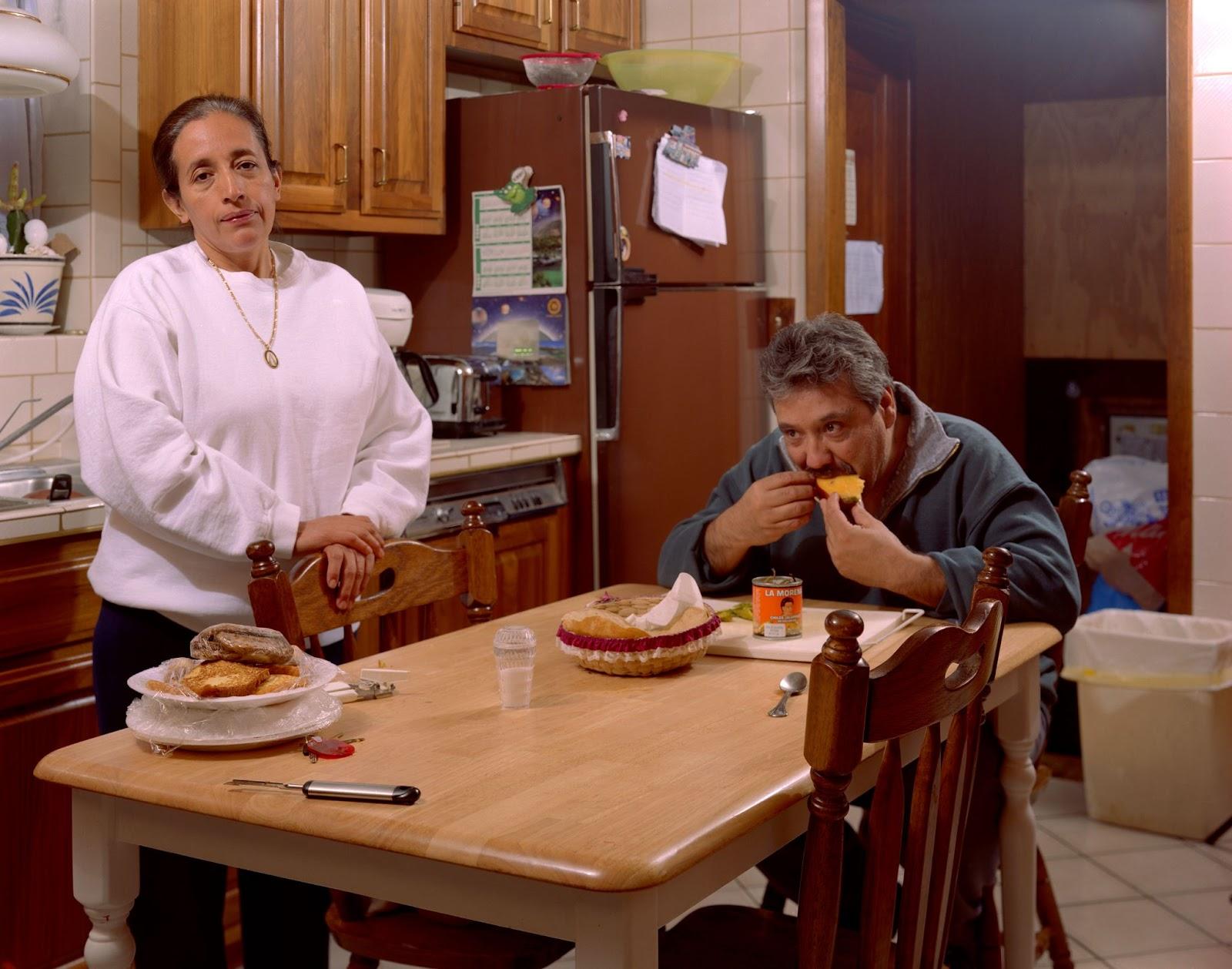 The image is a portrait of my parents in our kitchen in Berwyn, Illinois. My mother looks directly at the camera. She is casually dressed in a white sweatshirt, dark pants, and wears a long golden chain necklace with an enamel pendant of the Virgin of Guadalupe. She stands behind a wooden dining table with her hands resting on top of a chair. In front of her is a dish of assorted breads wrapped in plastic. On her left, my father is sitting down. He is eating a mango. His elbows are on the table. A small can of La Morena chiles and a basket of tortillas are within his reach. The walls and countertops of the kitchen are a white tiled brick pattern. The wooden cabinets give the room a sense of warmth. Behind them, magnets holding various papers decorate the large brown refrigerator and a doorway leads to the basement. Spanish: La imagen es un retrato de mis padres en nuestra cocina en Berwyn, Illinois. Mi madre me mira directamente a la cámara. Ella está casualmente vestida con una sudadera blanca, pantalones oscuros, y tiene puesta una cadena dorada con un colgante esmaltado de la Virgen de Guadalupe. Ella está parada detrás de una mesa de comedor de madera con sus manos reposadas en la parte superior de la silla. En frente de ella hay un platón lleno de panes distintos envueltos en plástico. A su izquierda, mi padre está sentado. Él se está comiendo un mango. Sus codos están sobre la mesa. Una lata pequeña de chiles marca La Morena y una canasta de tortillas están a su mano. Las paredes y la barra de la cocina son de un patrón de ladrillos hechos de cerámica blanca. Los gabinetes de madera le dan una sensación de calidez al cuarto. Detrás de ellos, imanes que sostienen varios papeles adornan el gran refrigerador marrón y la puerta que lleva al sótano.