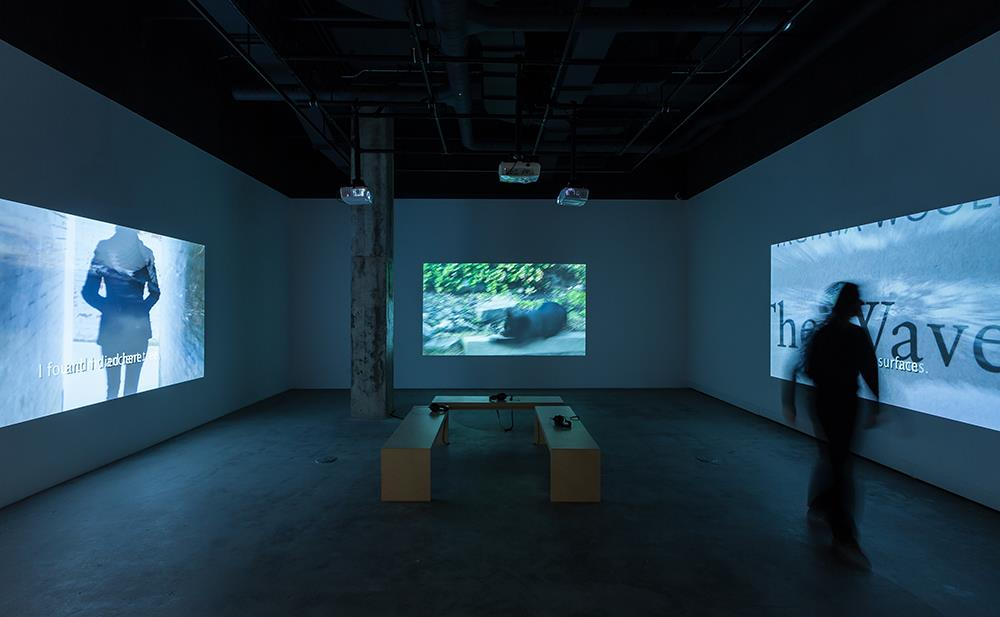 three walls with video projections and benches