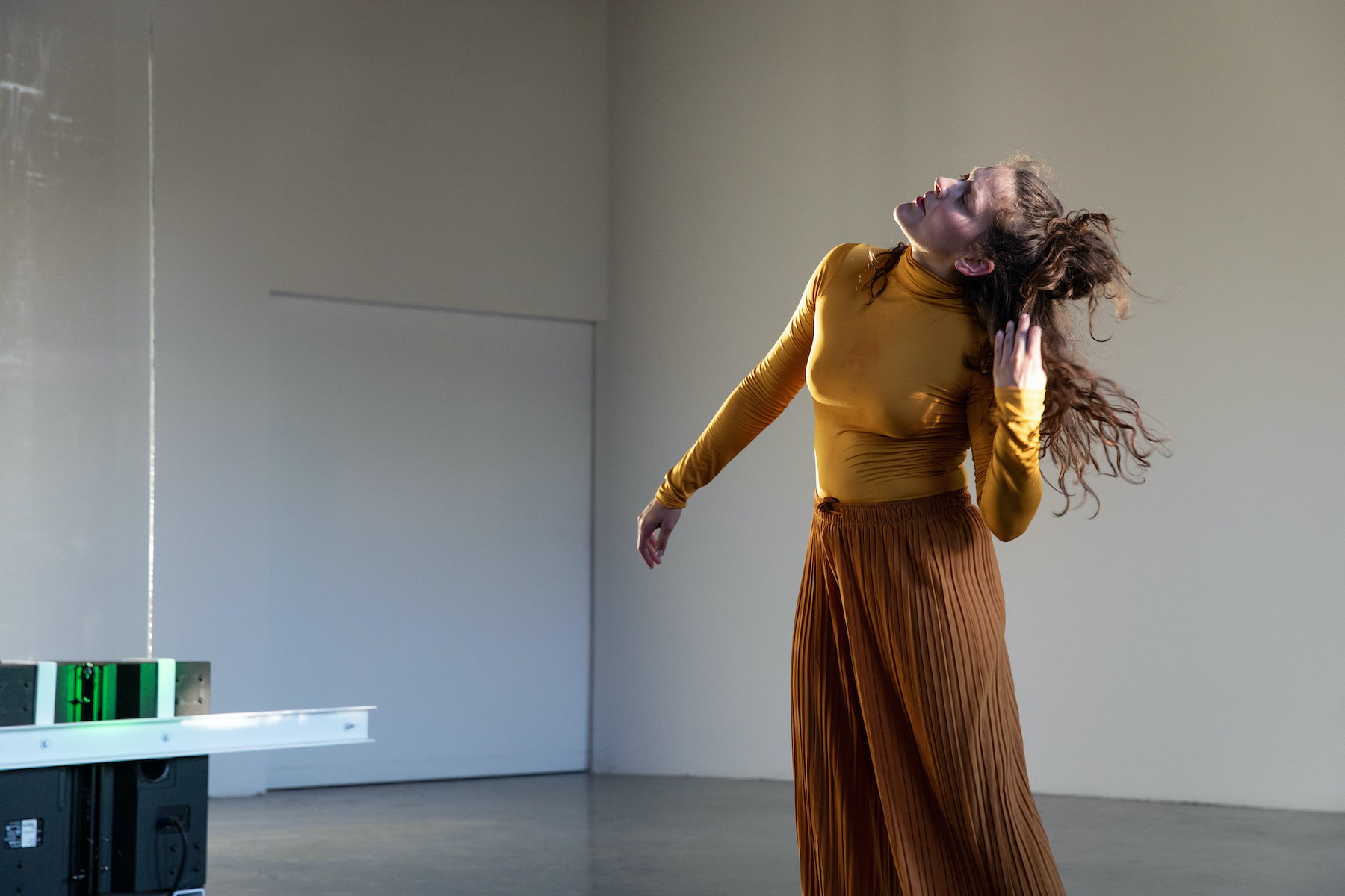 A woman pulls her head back while swinging to the side in a performance.
