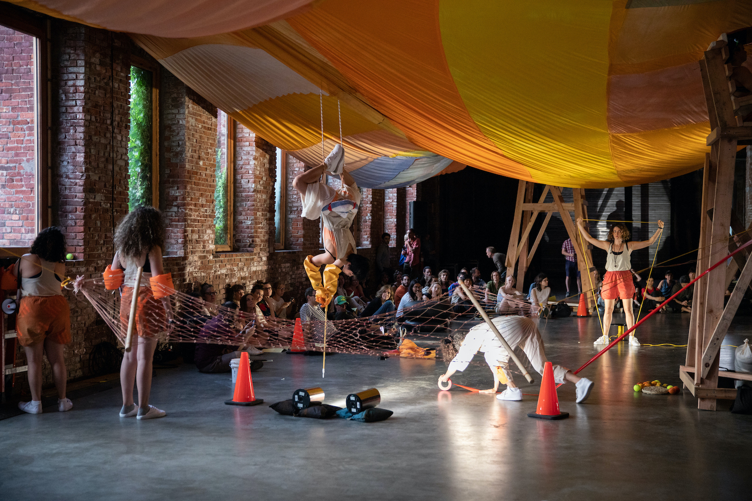 Five female performers enact various movements underneath a massive installation of hand-dyed parachute fabric.