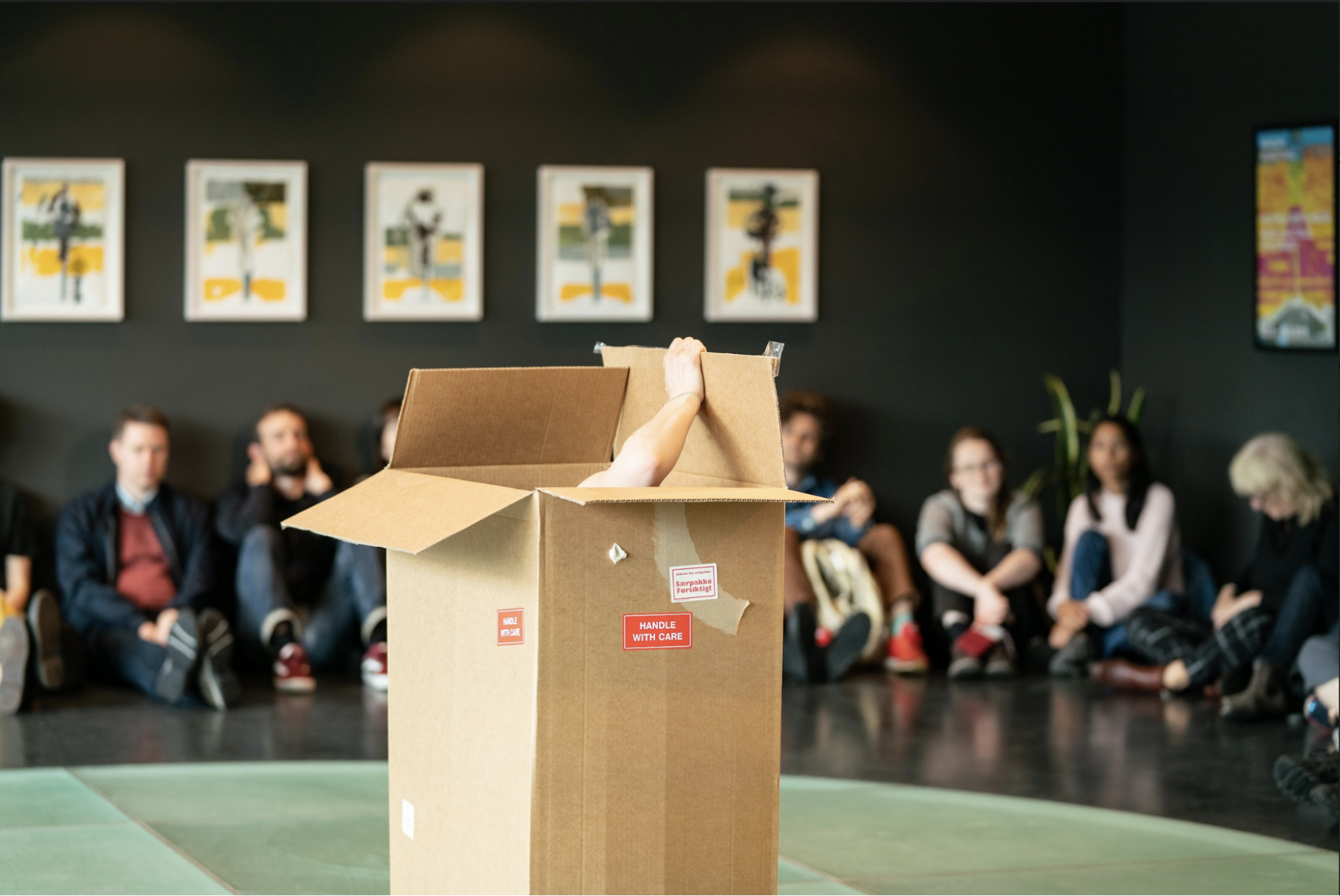 There is a large brown cardboard box in the foreground with the top open and a light skinned human arm extending out of it, opening one of the flaps. The background is out of focus and shows an audience of people sitting on the floor of a gray room with art on the walls.