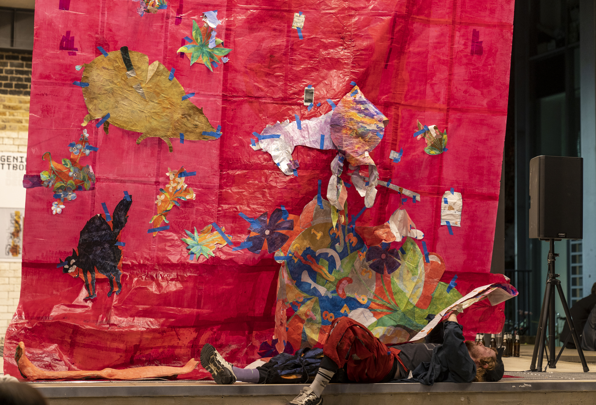 A white red haired man wearing landsknecht trousers and a baseball cap lays on his back reading a script. in the background, a large red backdrop made from paper, with drawings of a pig, a unicorn and a woried cartoon clock taped to its surface