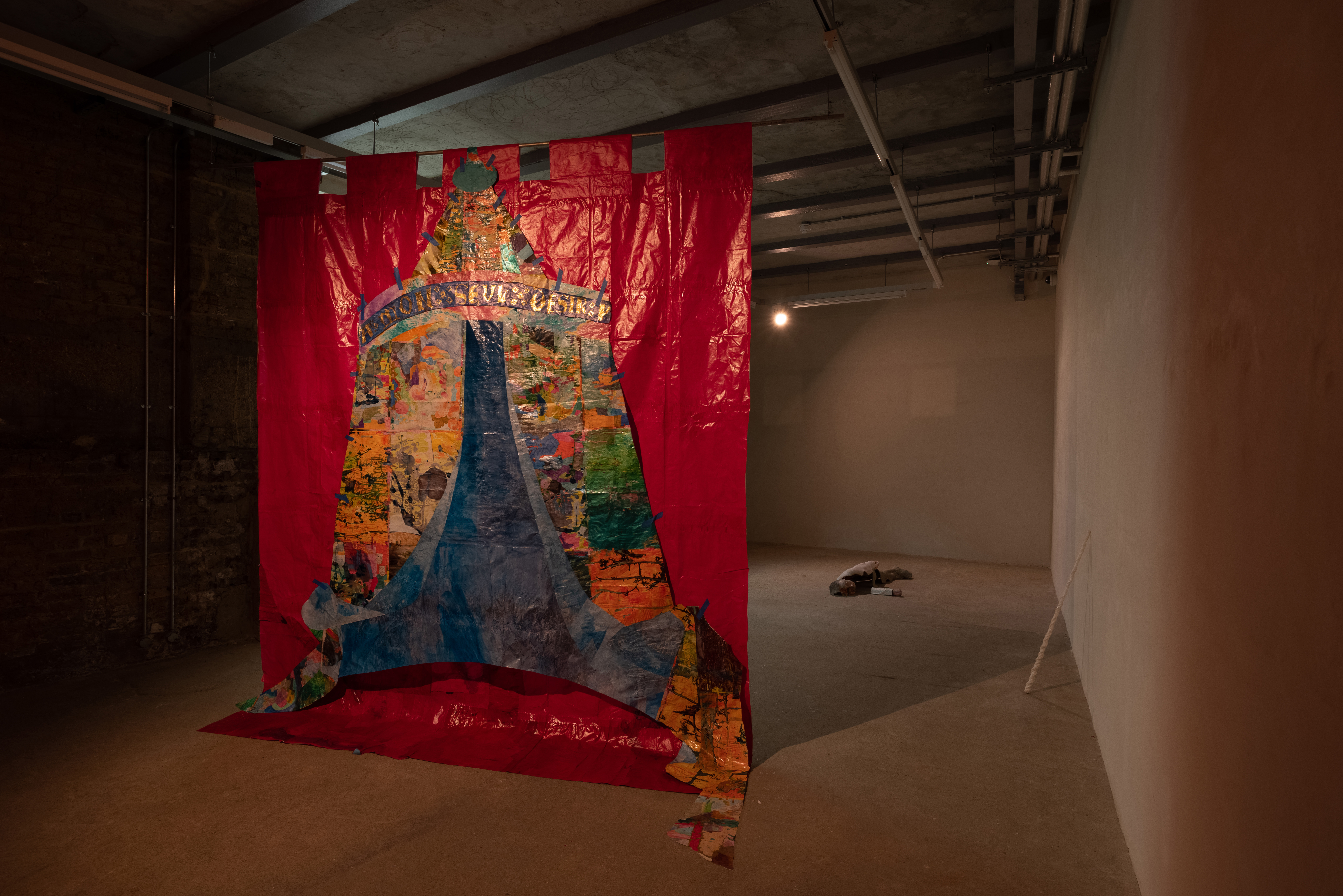 a large paper collage of a multicoloured tent on a red background hangs in the middle of a gallery. The words 'A Mon Seul Desire' run along the top of the tent. Behind the collage, a unicorn horn rests against the wall, and behind the horn is a sculpture of a reclining figure.