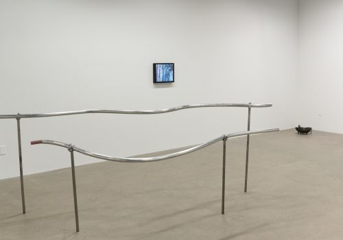 A gallery with concrete floors and white walls. A metal handrail sculpture is in the foreground. A monitor on the wall behind it shows a video work and a fountain sculpture in the far corner.