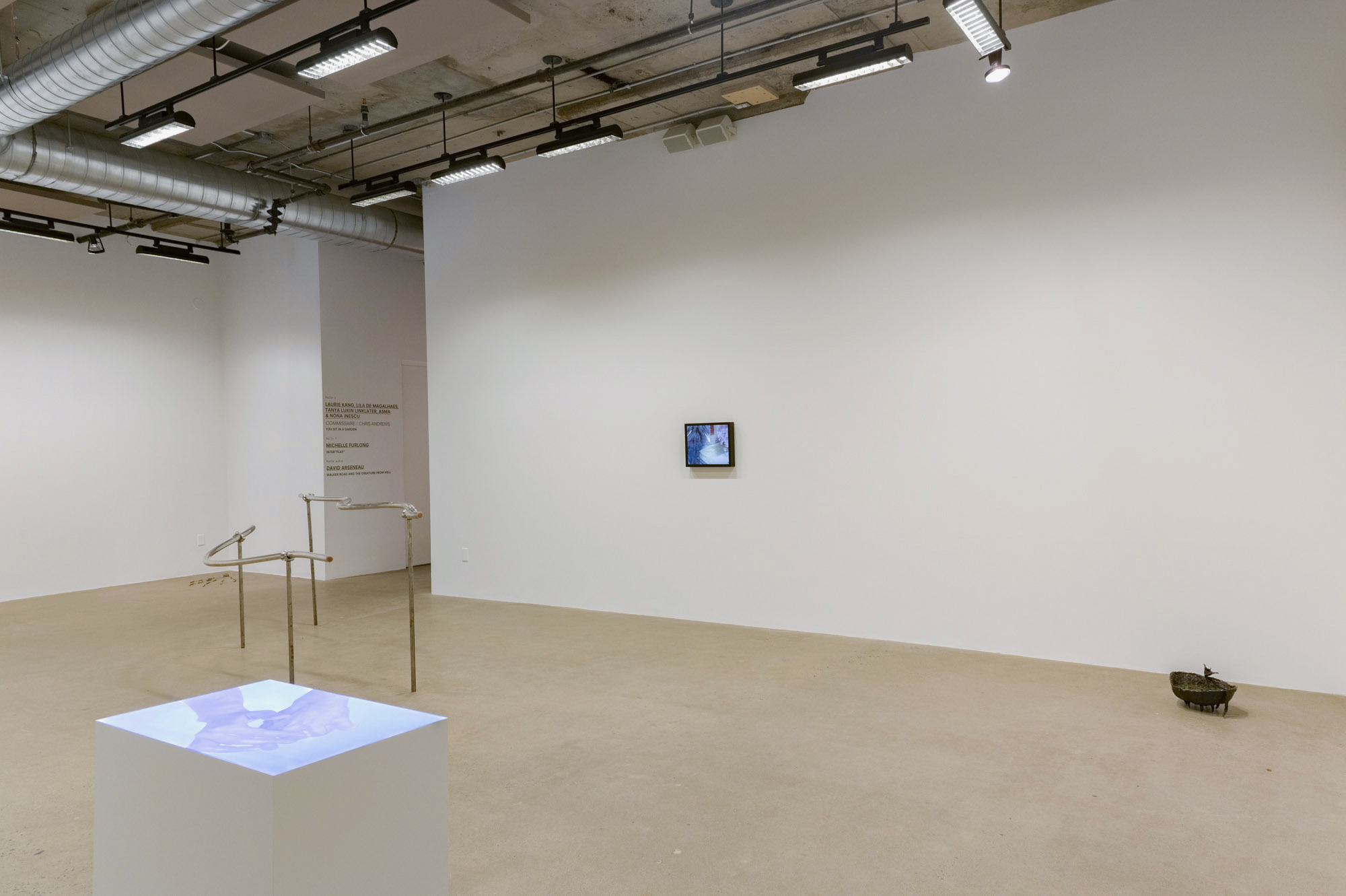 A gallery with concrete floors and high ceilings. Alt view of previous image, but we can now see a plinth with a projected video work featuring two hands in a blue light.