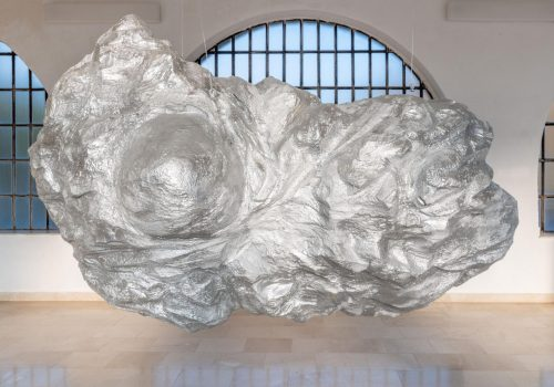 A large-scale silver object suspended in mid air, appears to levitate for a moment before it crashes on the floor surface. The stone-like object resembles an asteroid with some abstract human features: a torso and a single breast. The background is a minimal white space with arched windows.