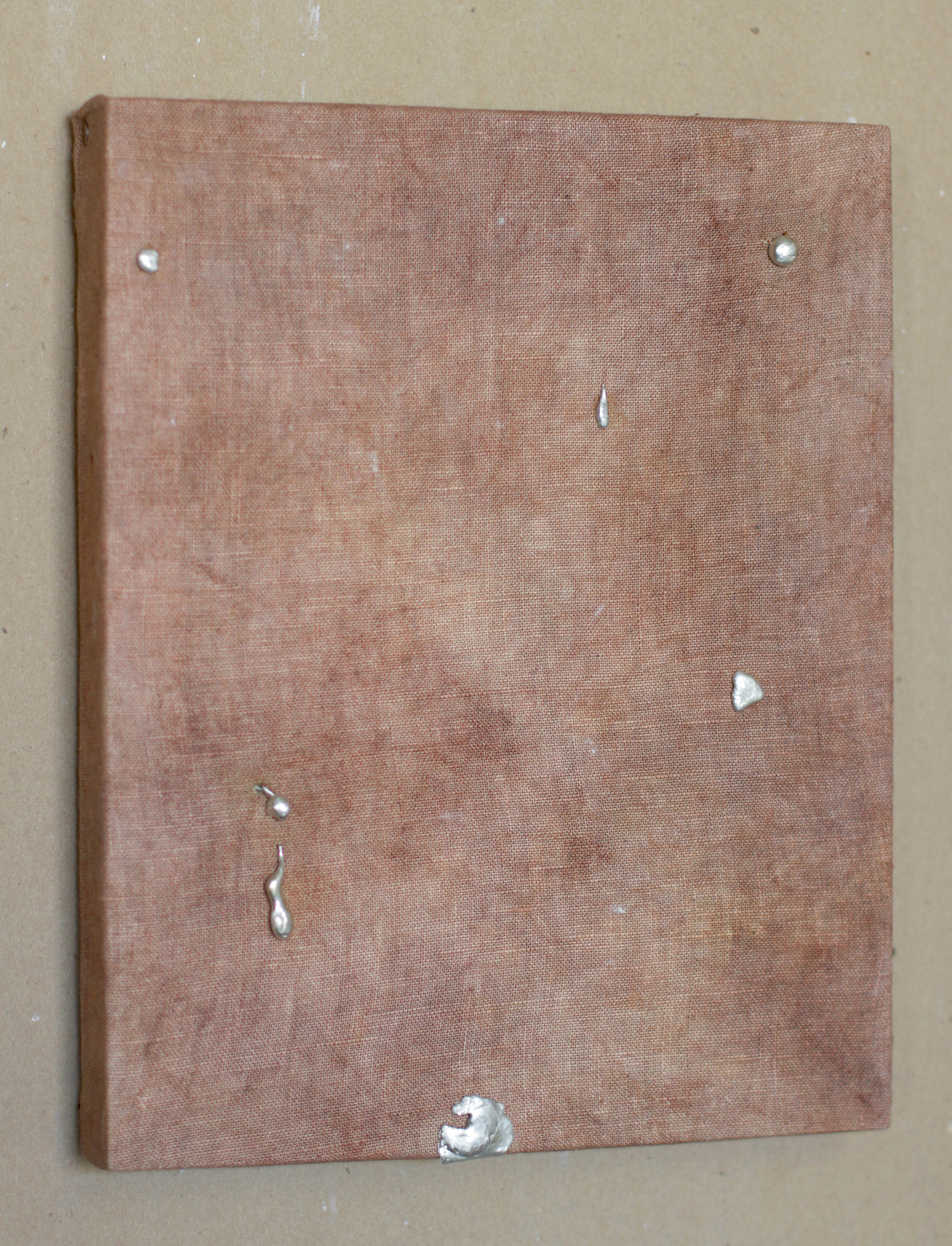 Rusty brown dyed linen stretched on canvas-stretcher with globs of silver metal adorned on top.