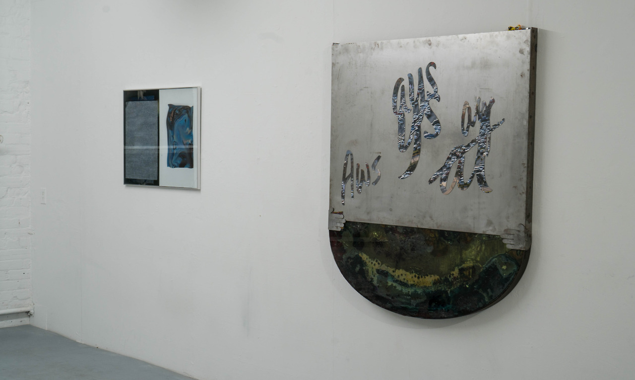 White gallery wall with two works hung side by side. The left work is a cool toned photographic diptych. The right work is rounded and mossy at the bottom with a silver plated sheet at the top, reading the word