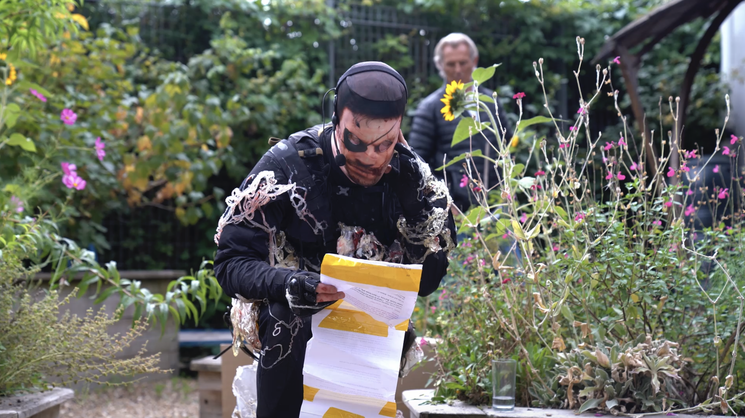 A man wearing tactical military gear kneels in a garden reading a script. He is covered in some kind of translucent spermatological substance and is wearing a nylon mask printed with the face of Venom Snake.