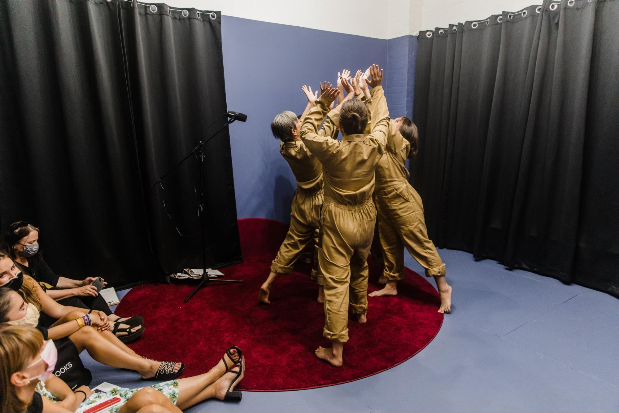 A group of five women in tan jumpsuits and bare feet face away from the camera and raise their hands together in a tight circle. A black microphone on a stand points towards them. The room is painted periwinkle blue with black curtains flanking the women and a circular maroon rug on the floor. To their left is a group of female audience members wearing face masks and sitting on the floor.